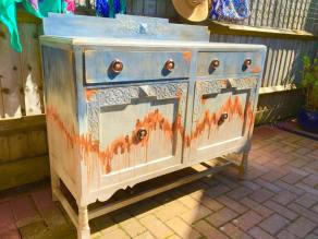 "SOLD - BERMUDA SKY. Beautiful old sideboard boosted back to life with beautiful shades of blue and peach with rose gold leaf. Very sturdy piece. H37 (+4"" for back piece) x W 48 x D 19"". Drawers are paper lined. Shelf in one side. Waxed finish. £175"