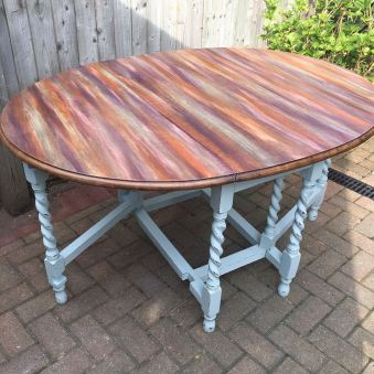 "SUNSET Drop leaf table. Tabletop blended in soft colours, legs distressed in duck egg blue. Dimensions when folded - Length 39"" Width 18.5"" Height 29"". When unfolded - Length 52"" Width 39"". A beautiful, solid vintage table. £275."
